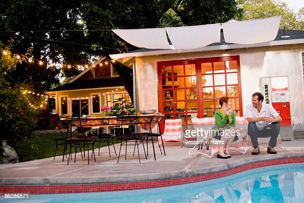 couple sitting beside swimming pool - jessamyn harris stock pictures, royalty-free photos & images