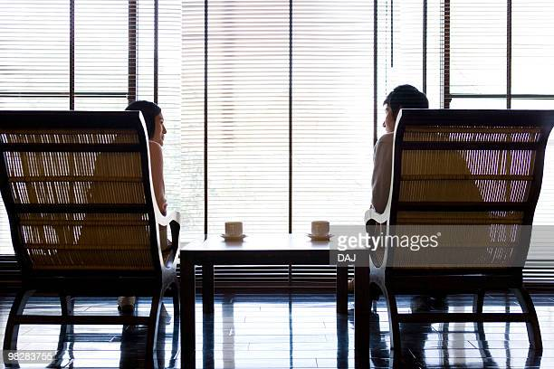 couple sitting beside the window - mid adult couple stock pictures, royalty-free photos & images