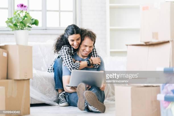 couple assis entre les zones d'et à l'aide d'un ordinateur portable - euphorique photos et images de collection