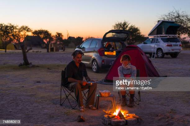 Couple Sitting Bonfire On Field Against Sky During Sunset
