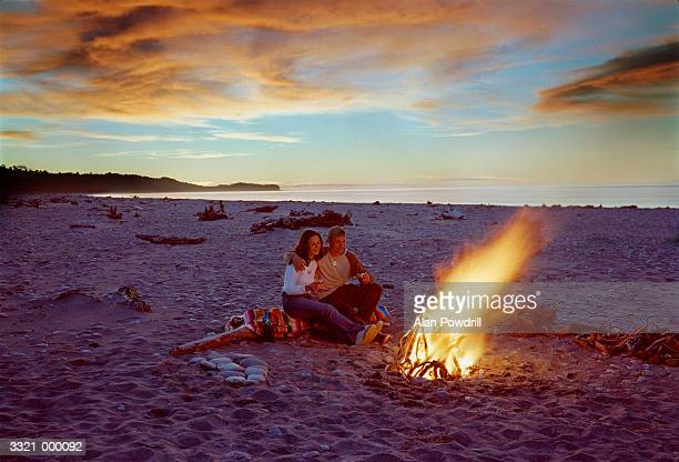 Couple Sitting by Beach Fire