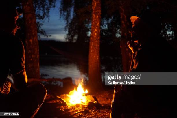 couple sitting by bonfire during night in forest - lagerfeuer stock-fotos und bilder