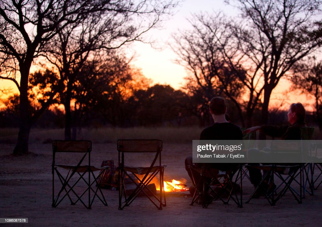 Couple Sitting By Campfire Against Sky During Sunset : Stockfoto