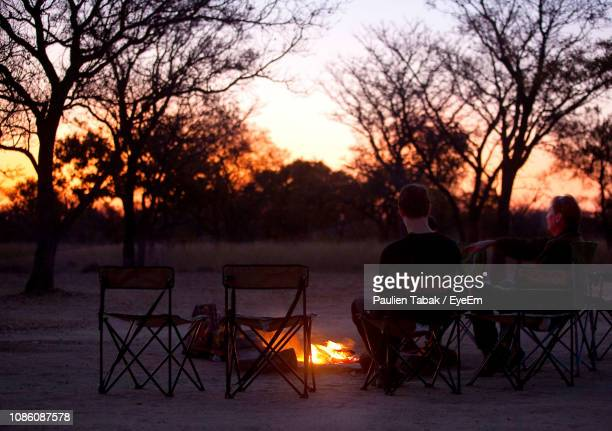 Couple Sitting By Campfire Against Sky During Sunset