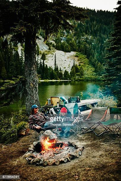 Couple sitting by campfire near mountain lake