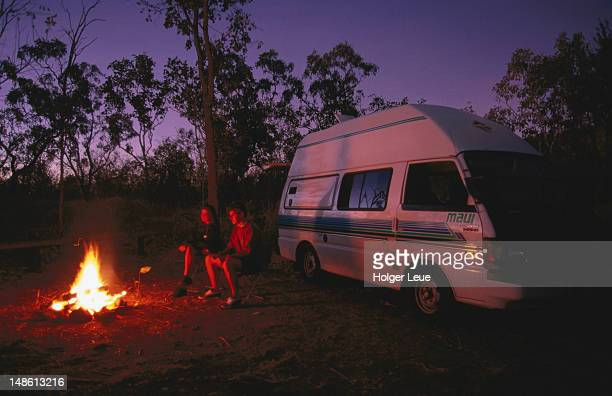 Couple sitting by campfire outside campervan.