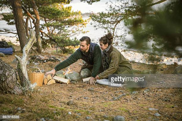 Couple sitting by fire pit at camping ground in forest
