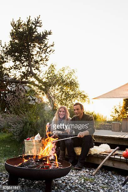 couple sitting by fire pit in garden - fire pit stock pictures, royalty-free photos & images