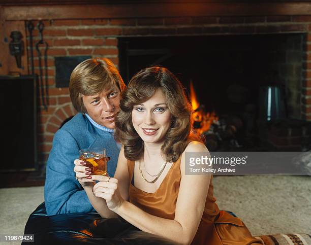 Couple sitting by fireplace holding liqueur, smiling