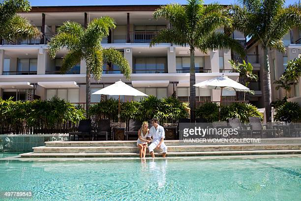 Couple sitting by resort pool wedding ceremony