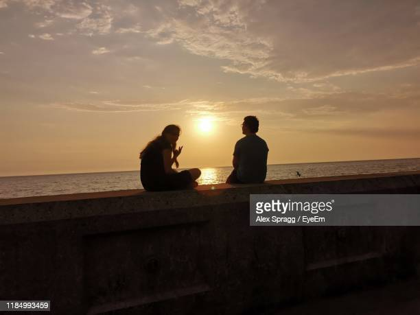 couple sitting by sea against sky during sunset - visit stock pictures, royalty-free photos & images