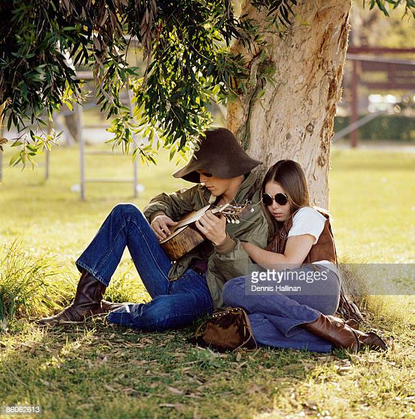 Couple sitting by tree playing guitar