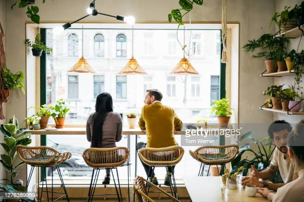 couple sitting by window in quirky café - diversity stock pictures, royalty-free photos & images