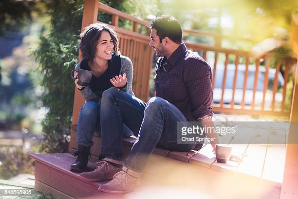 Couple sitting chatting on porch step