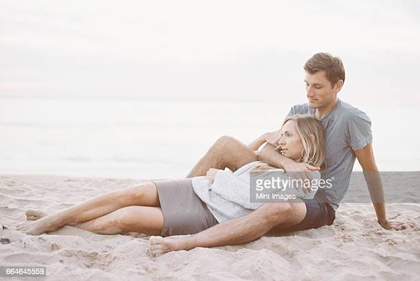 A couple sitting close on a beach, a man and woman with their arms around each other and heads together.