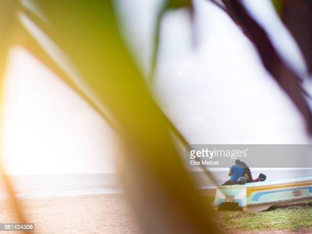 couple sitting closely together on Negombo beach