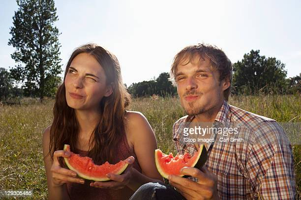 Couple sitting eating melon in field