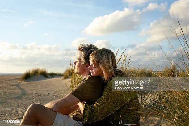 couple sitting embracing on beach - dos personas fotografías e imágenes de stock