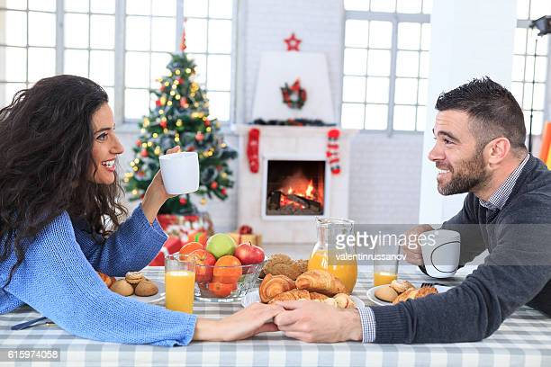 Couple sitting face to face and drinking coffee at home