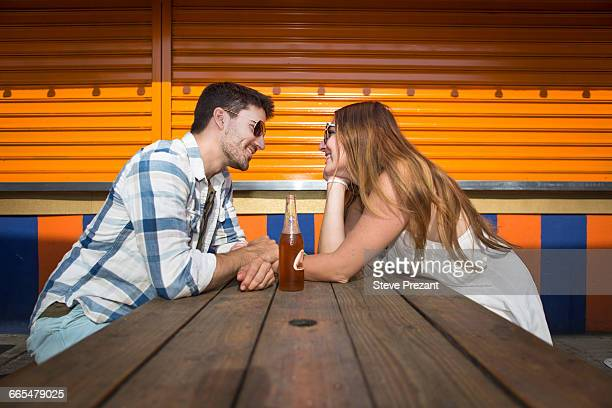 couple sitting face to face at picnic table, coney island, brooklyn, new york, usa - picnic table stock pictures, royalty-free photos & images
