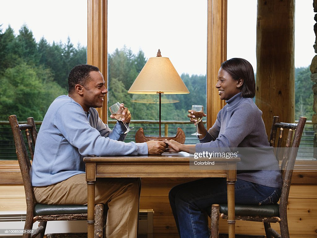 Couple sitting face to face at table, holding hands and drinking wine : Foto stock