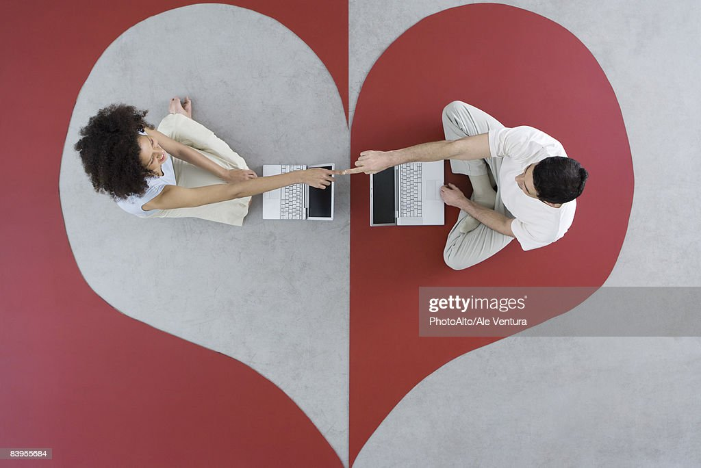 Couple sitting face to face with laptop computers on heart shape, touching fingers, overhead view : Stock Photo
