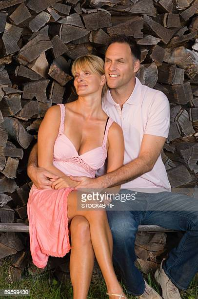 Couple sitting front of wood pile