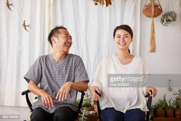 A couple sitting in a chair with a smile.