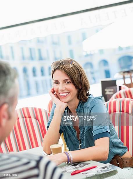 couple sitting in a city cafe smiling - zuid europese etniciteit stockfoto's en -beelden