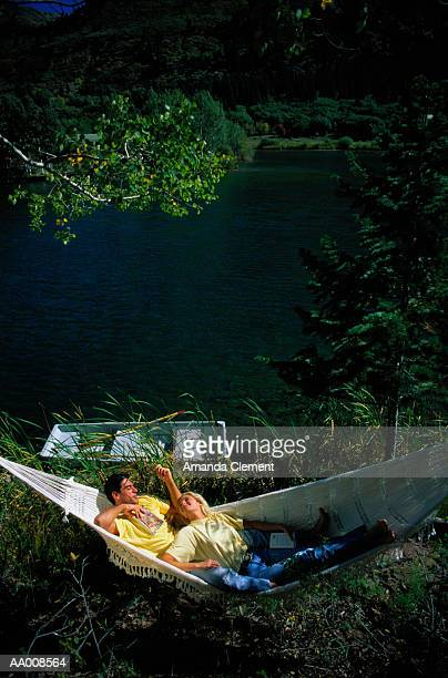 Couple Sitting in a Hammock by a Lake