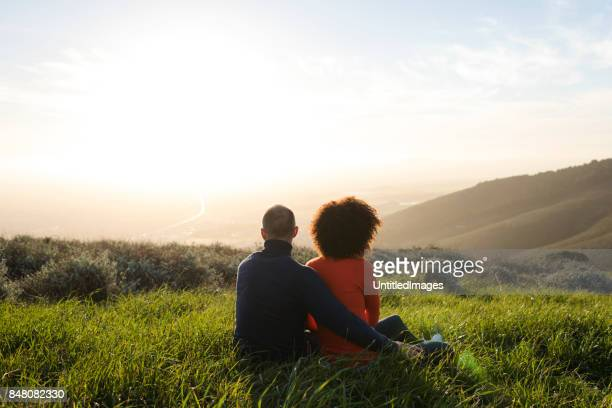couple sitting in a meadow and watching the sunset - images stock pictures, royalty-free photos & images