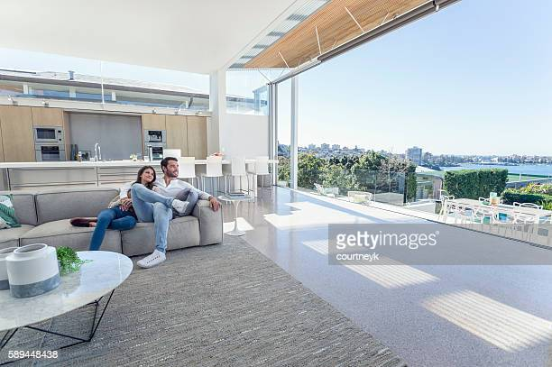 couple sitting in a modern open plan house. - luxury stock pictures, royalty-free photos & images