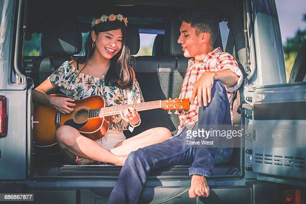 Couple Sitting In Back Of Car Playing Guitar