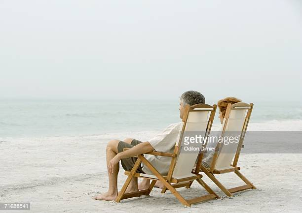 Couple sitting in beach chairs, looking at view
