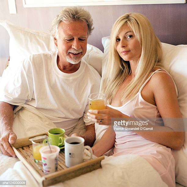 couple sitting in bed, man holding tray of drinks - gold digger stock photos and pictures