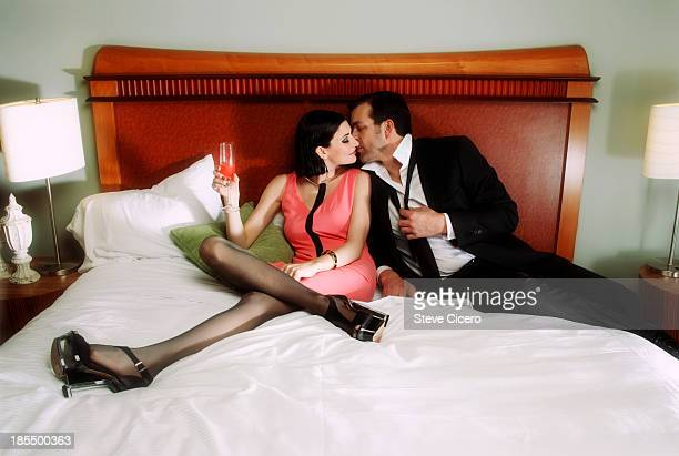 couple sitting in bed ready to kiss - men wearing stockings stock photos and pictures