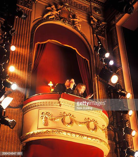 Couple sitting in box in theatre, low angle view