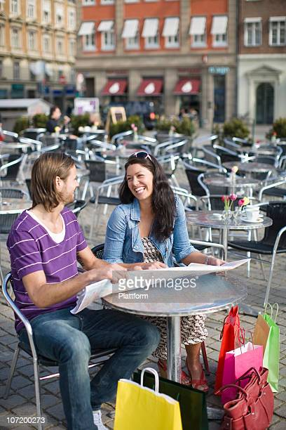 Couple sitting in cafe holding map, laughing