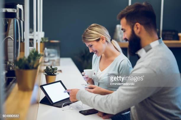Couple assis dans le café avec tablette numérique et surfer sur le web