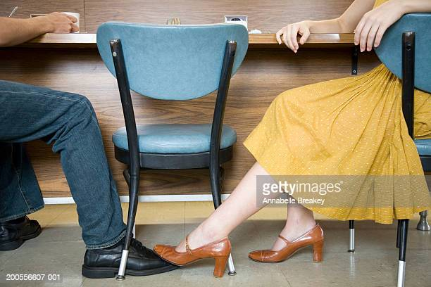 Couple sitting in cafe, woman playing footsie with man