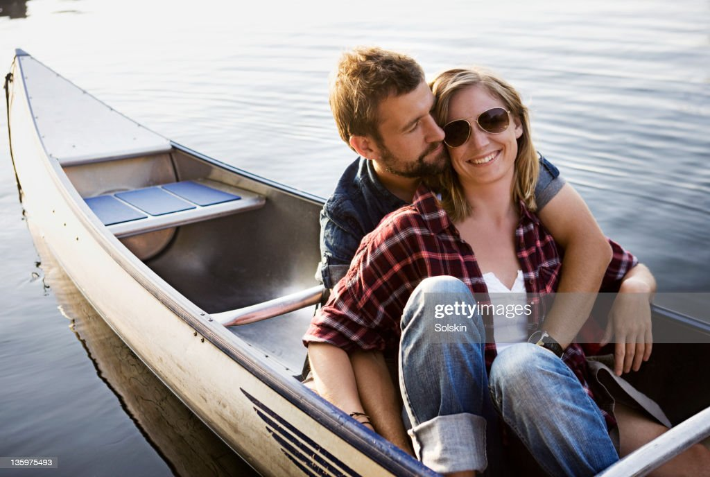 Couple sitting in canoe, hugging : Stock Photo