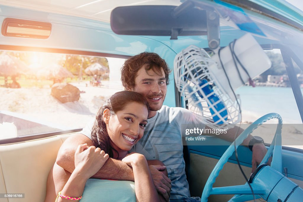 Couple sitting in car on beach : Foto stock