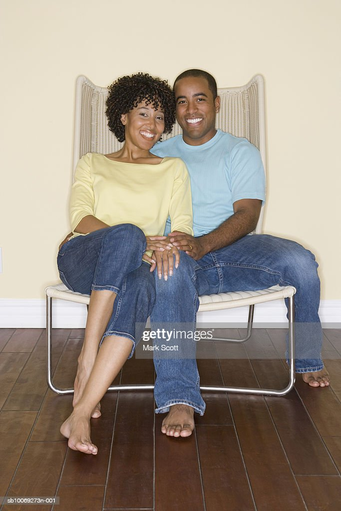 Couple sitting in chair together, portrait : Stockfoto