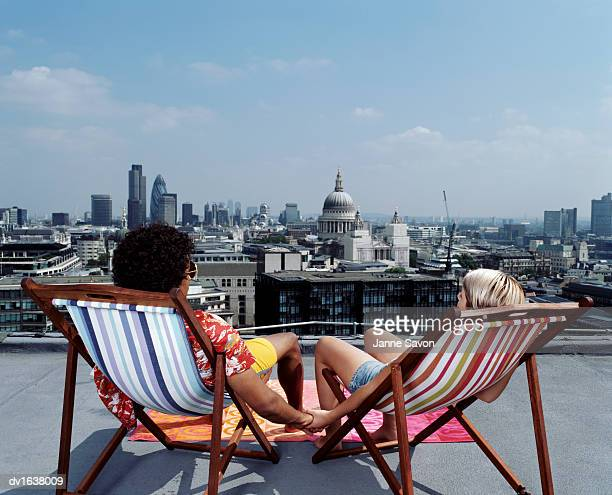 Couple Sitting in Deck Chairs and Holding Hands Facing a Skyline of London