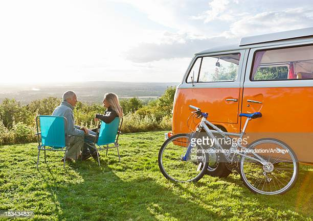 couple sitting in deck chairs by camper van - cadeira dobrável - fotografias e filmes do acervo