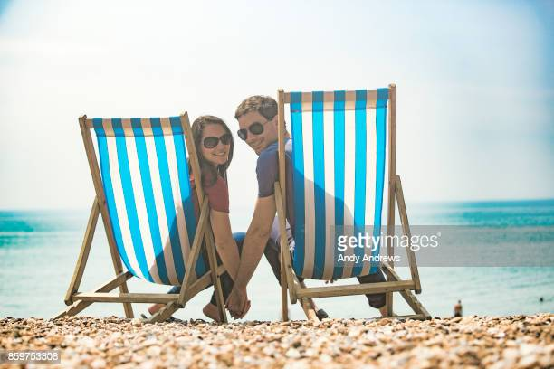 Couple sitting in deck chairs on a beach
