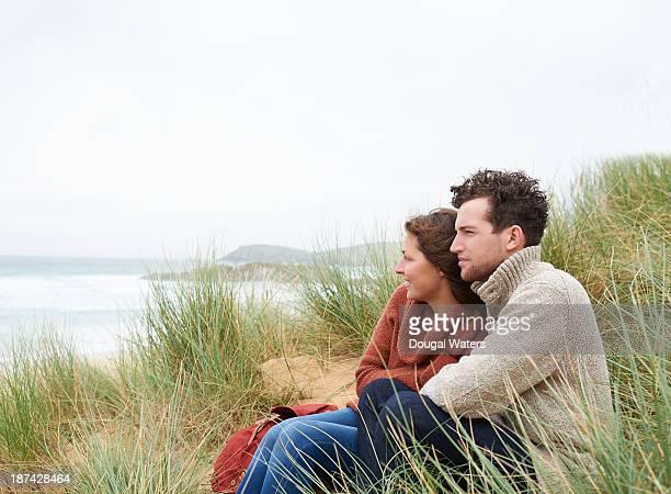 Couple sitting in dunes on Atlantic coastline.