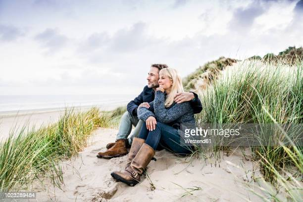 couple sitting in dunes - mid adult stock pictures, royalty-free photos & images