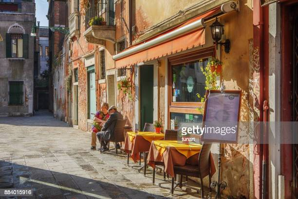 couple sitting in front of a cafe in venice, italy - italian culture stock pictures, royalty-free photos & images