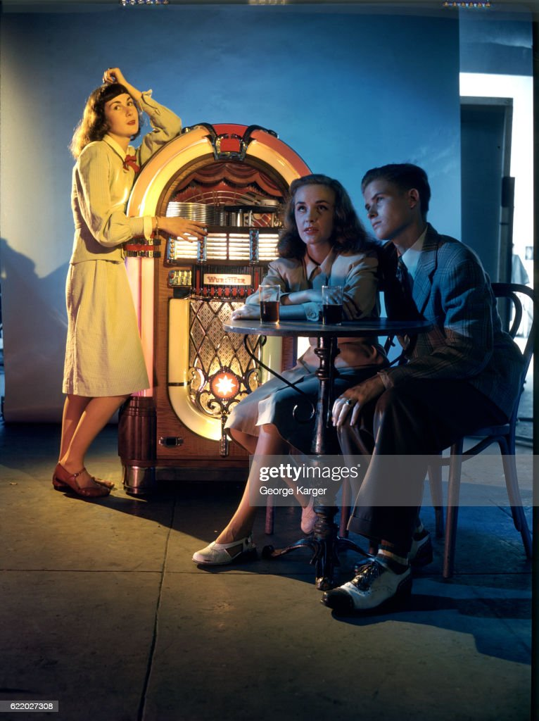 Couple sitting in front of a woman at the juke box in a bar, New York City, 1947.